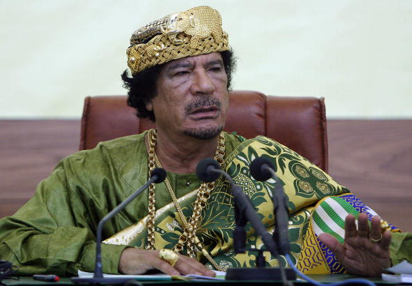 Gaddafi looks about 4x as rich as Buffet sporting all gold everything and Louis Vuitton shades