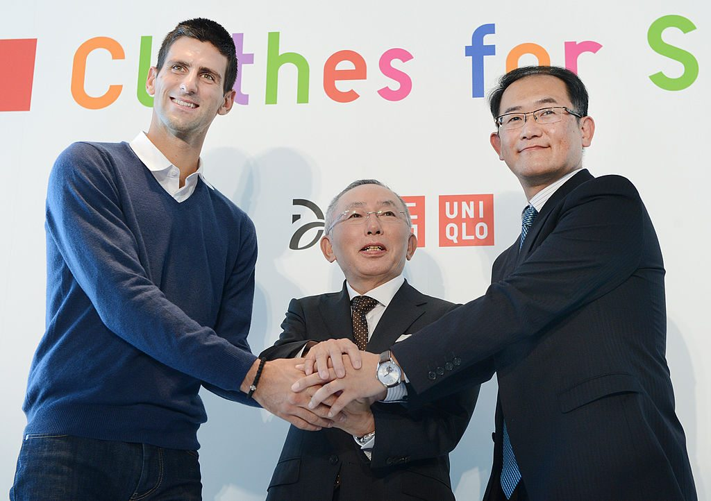 Novak Djokovic (L) shakes hands with Tadashi Yanai