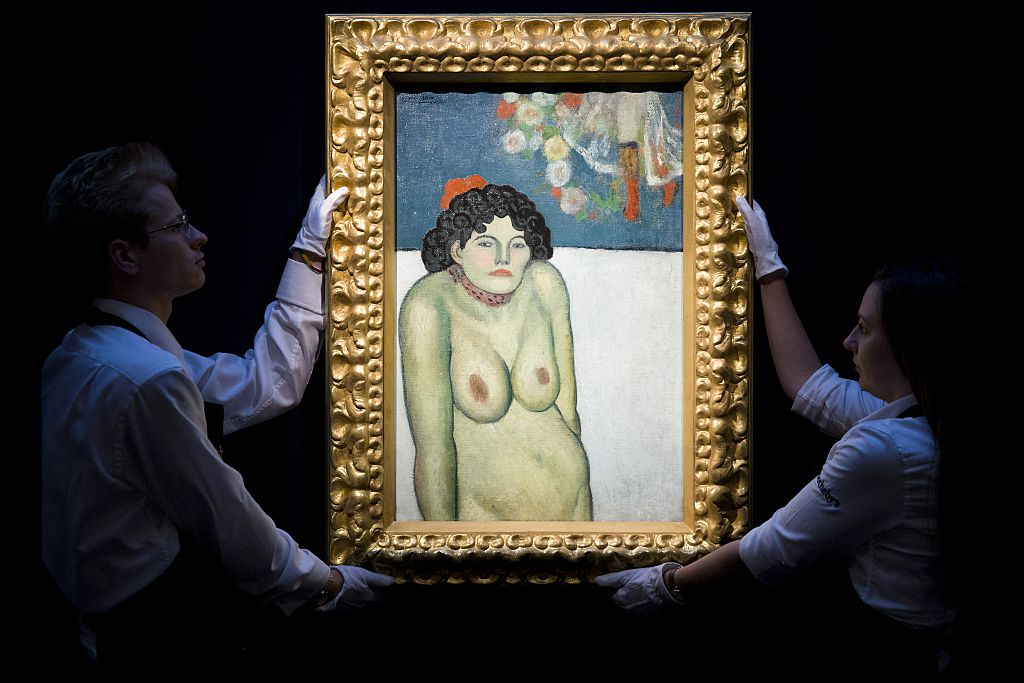 Employees of Sotheby's auction house pose for photographers with the 1901 painting 'La Gommeuse' by Spanish artist Pablo Picasso, estimated to sell for 60 million USD (53 million euro, 39 million GBP) at auction in New York, during a press preview in London on October 9, 2015 . AFP PHOTO / JUSTIN TALLIS  --  RESTRICTED TO EDITORIAL USE, MANDATORY MENTION OF THE ARTIST UPON PUBLICATION, TO ILLUSTRATE THE EVENT AS SPECIFIED IN THE CAPTION        (Photo credit should read JUSTIN TALLIS/AFP/Getty Images)