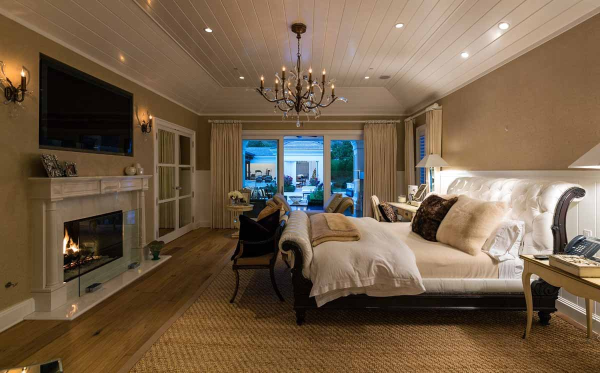 this-master-bedroom-features-a-massive-sleigh-bed-and-pale-wood-floors