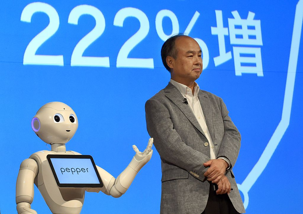"SoftBank Group founder and CEO Masayoshi Son (R) listens to the company's robot ""Pepper"" (L) during a press conference announcing the company's financial results in Tokyo on August 6, 2015. Japanese telecommunication company SoftBank Group announced an increase of 175 percent in net profit after the first quarter of the fiscal year 2016, with a 10 percent increase in revenues and non-operating items. AFP PHOTO / TOSHIFUMI KITAMURA (Photo credit should read TOSHIFUMI KITAMURA/AFP/Getty Images)"