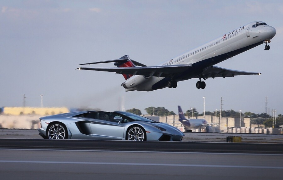 MIAMI, FL - JANUARY 28: A new Lamborghini Aventador LP700-4 Roadsters is seen as it is driven along the south runway at the Miami International Airporton January 28, 2013 in Miami, Florida. The world wide unveiling of the new luxury super sports cars took place at the airport. (Photo by Joe Raedle/Getty Images)