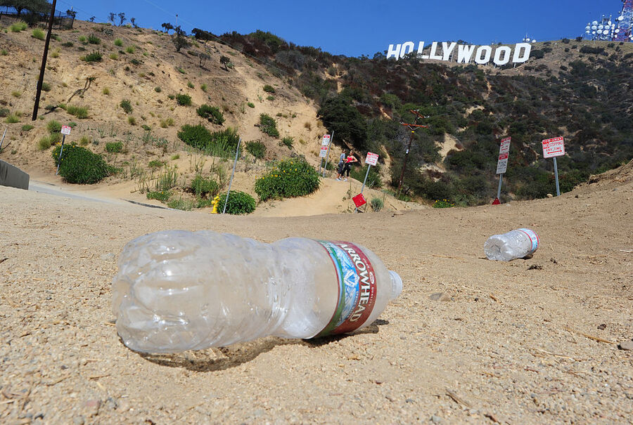 With AFP Story by Michael THURSTON: US-environment-technology-tourism Empty water bottles litter the ground at a popular Hollywood sign viewing area in the residential Hollywood Hills section of Hollywood, California, September 21, 2011. Travelers have long flocked to have their pictures taken with the vast sign behind them -- but with the advent of satellite navigation and Google Earth, they have begun to invade the Hollywood Hills neighborhood like never before. AFP PHOTO / ROBYN BECK (Photo credit should read ROBYN BECK/AFP/Getty Images)
