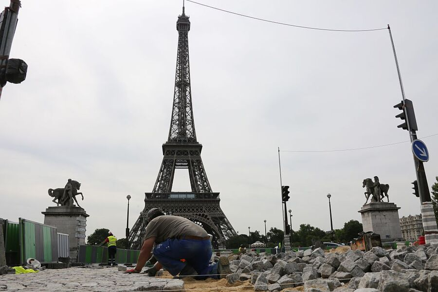 A worker lays historical cobblestone pavement on the road at Place de Varsovie by the Eiffel Tower in Paris on June 26, 2015. AFP PHOTO / LUDOVIC MARIN (Photo credit should read LUDOVIC MARIN/AFP/Getty Images)