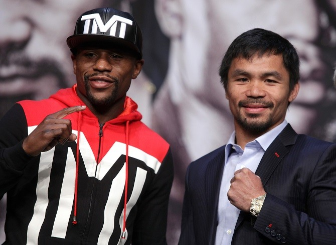 WBC/WBA welterweight champion Floyd Mayweather Jr. (L) of the US and WBO welterweight champion Manny Pacquiao of the Philippines pose during a news conference at the KA Theatre at MGM Grand Hotel & Casino on April 29, 2015 in Las Vegas, Nevada. The two will face each other in a unification bout on May 2, 2015 in Las Vegas.   AFP PHOTO / JOHN GURZINSKI        (Photo credit should read JOHN GURZINSKI/AFP/Getty Images)
