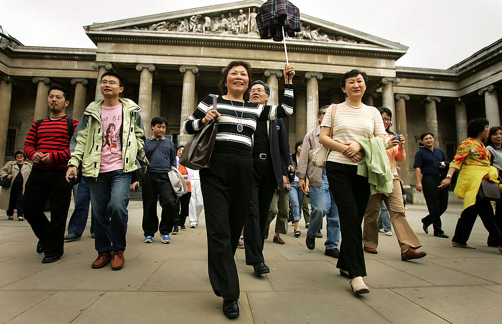 LONDON - JULY 25: Chinese tourists visit the British Museum on July 25, 2005 in London. In 2004, 135,000 Chinese citizens traveled to the UK but were only allowed to do so for business or study reasons or to visit family. Today saw the arrival of the first 80 Chinese tourists who flew into London Heathrow on a package tour. (Photo by Bruno Vincent/Getty Images)