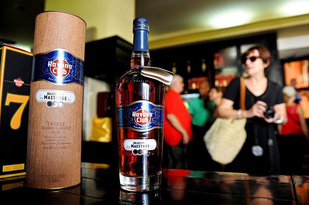 Tourists buy Cuban rum in a store of Havana, on October 18, 2016. US President Barack Obama sought to cement his administration's rapprochement with Cuba, unveiling a new round of loosened trade rules, including lifting limits on rum and cigar imports. / AFP / YAMIL LAGE (Photo credit should read YAMIL LAGE/AFP/Getty Images)